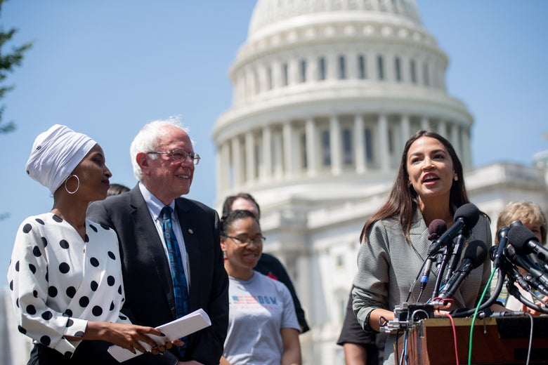 Ilhan Omar and Bernie Sanders look on as Alexandria Ocasio-Cortez speaks into several microphones at a podium. The Capitol dome and several other people are behind them.