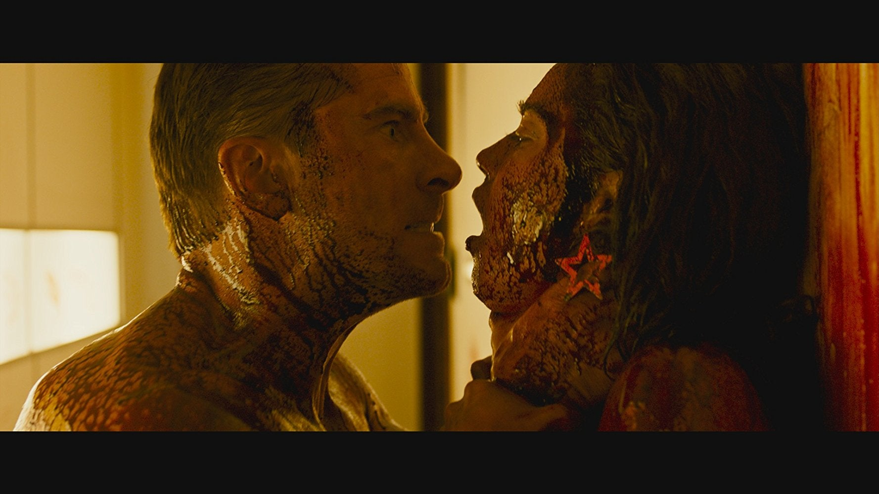 Kevin Janssens and Matilda Lutz in Revenge. Janssens grips Lutz by the throat and stares at her. They are both covered in blood.