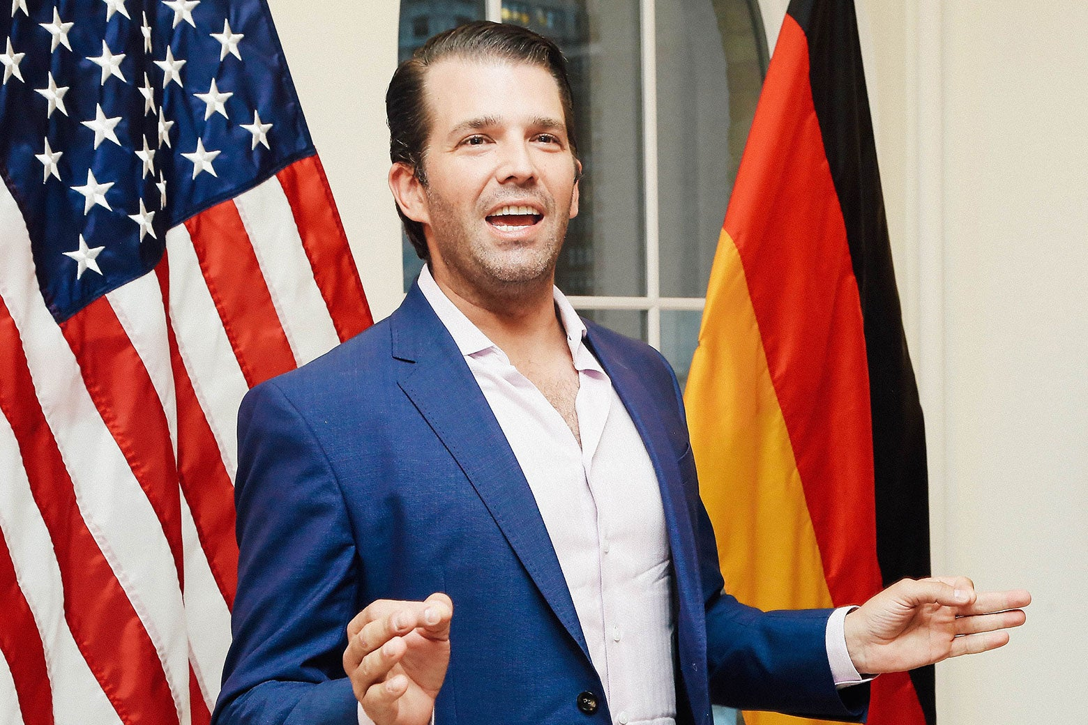 Donald Trump Jr. in front of American and German flags.