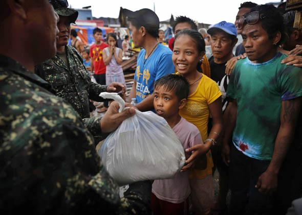 A young Filipino girl smiles as she and her brother receive their first bag of food aid at a center in Tacloban in the aftermath of Typhoon Haiyan on November 14, 2013 in Tacloban, Philippines.