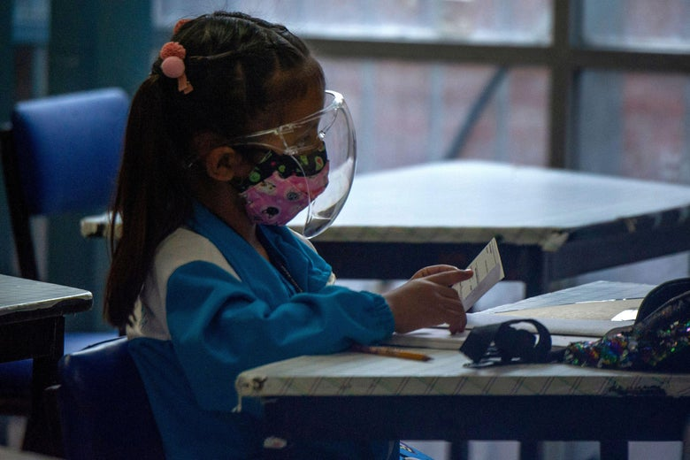 An elementary-school student sits at a desk wearing a mask and face visor.