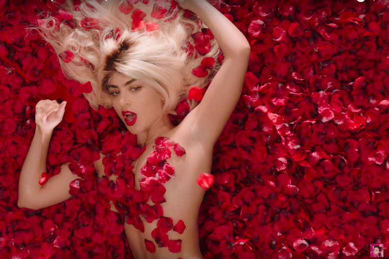 Charli XCX nude, covered in bright red rose petals.