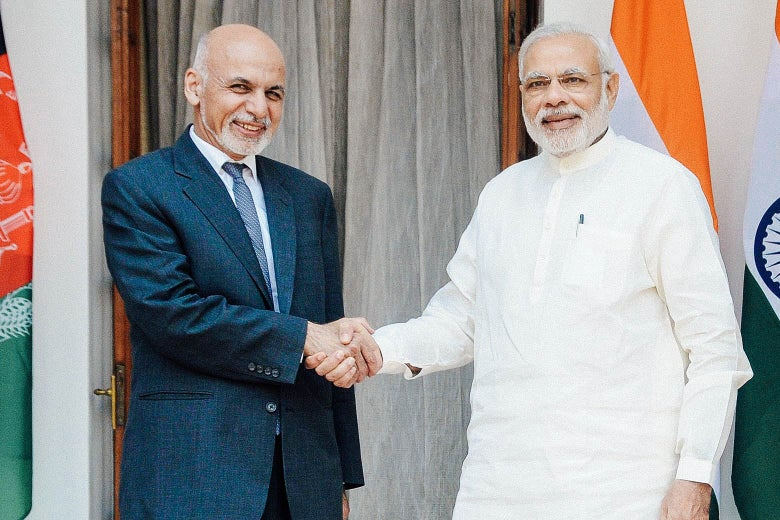 Two men shake hands and pose for the camera in front of flags for Afghanistan and India.