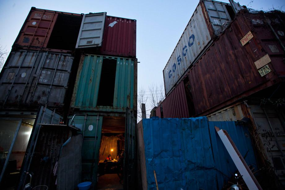 A child (bottom) does homework inside a shipping container serving as his accommodation, in Shanghai March 4, 2013. The containers, which house different families, were set up by the landlord, who charges a rent of 500 yuan ($ 80) per month for each container.