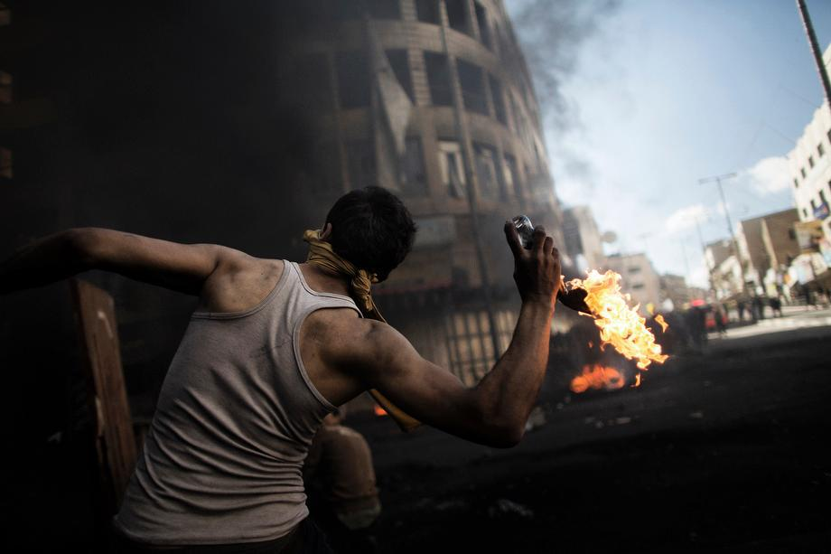 A Palestinian demonstrator throws a petrol bomb towards Israeli security forces during clashes in the West Bank city of Hebron on April 4, 2013.