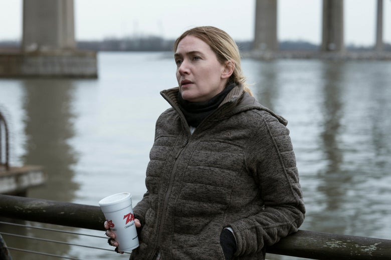 Kate Winslet as Mare looking pensive as she leans against a railing by the river. She is wearing a heavy coat and holding a takeout soda cup.