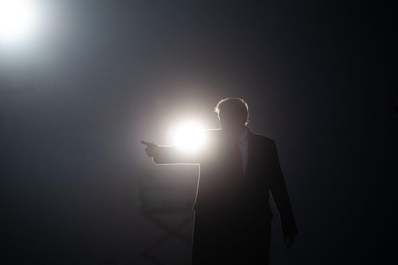 Donald Trump on a rally stage in front of a spotlight.