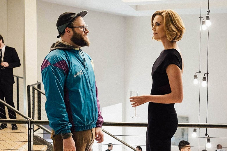 Seth Rogen wears a windbreaker and Charlize Theron wears a chic black dress as they talk at a party in a still from the movie.