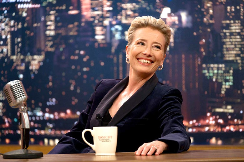 In this still from Late Night, Emma Thompson sits behind the desk of a late-night TV show with a mug and microphone. She's smiling and looking off-camera.