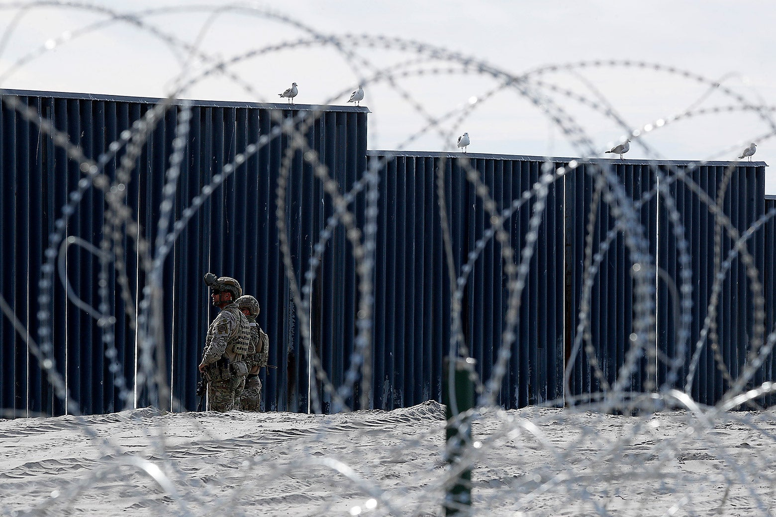 U.S. Border Patrol officers stand guard beside the border wall in Imperial Beach, California on Nov. 15.
