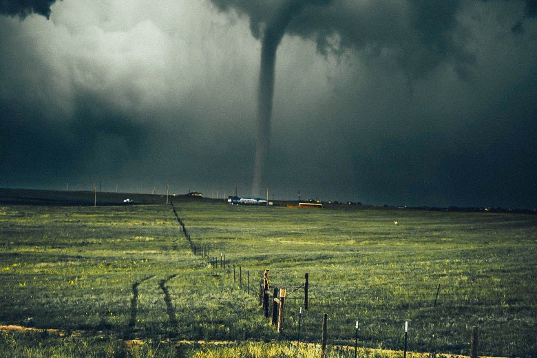 A tornado touches down near a field.