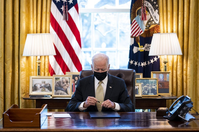 Biden caps a pen while seated at the Resolute Desk wearing a black mask