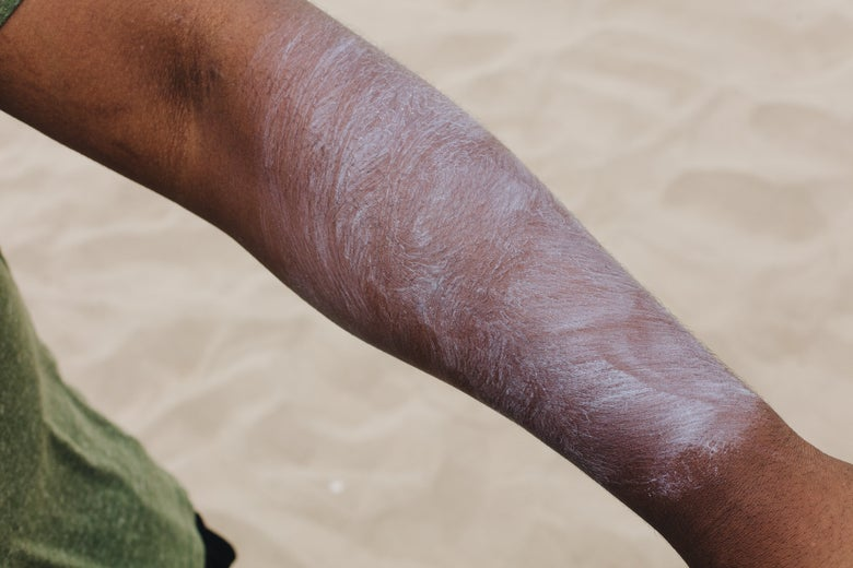 sunscreen on an arm, partially rubbed in