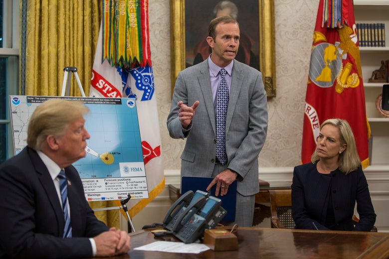 Brock Long speaks in front of a map of the trajectory of Hurricane Florence in the Oval Office. Donald Trump and Kirstjen Nielsen sit on either side of him.