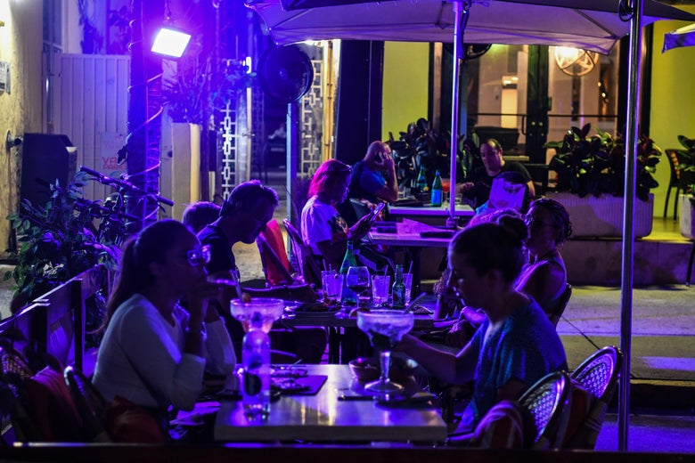 Diners eat outside at night under bluish lights.