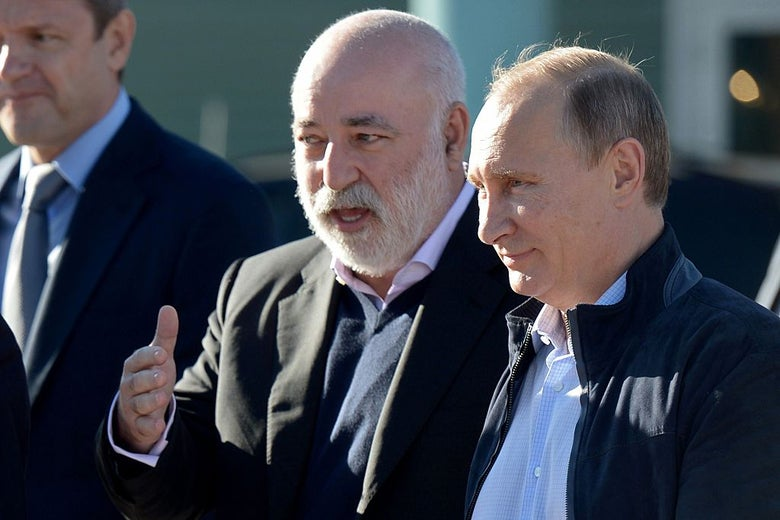 Viktor Vekselberg gestures with his right hand while speaking to Vladimir Putin.
