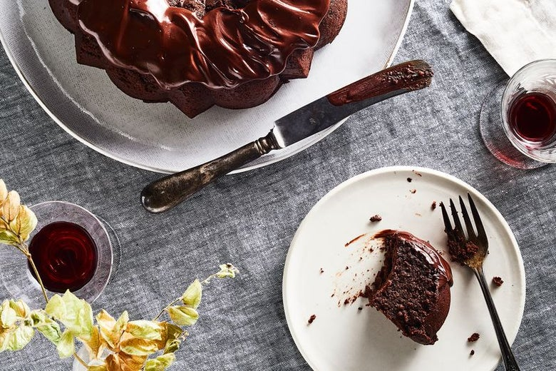A slice of chocolate quinoa cake drenched in ganache sits on a plate, next to the whole cake and some Passover wine.