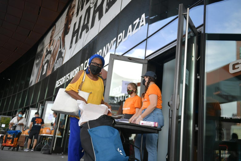 A woman pushes a rolling card with produce away from a line of folding tables set up in front of the Barclays Center.