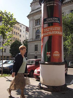 "A woman in downtown Budapest walks by a European Parliament campaign poster for the Fidesz party that reads: ""Our message to Brussels: Respect Hungarians!"""