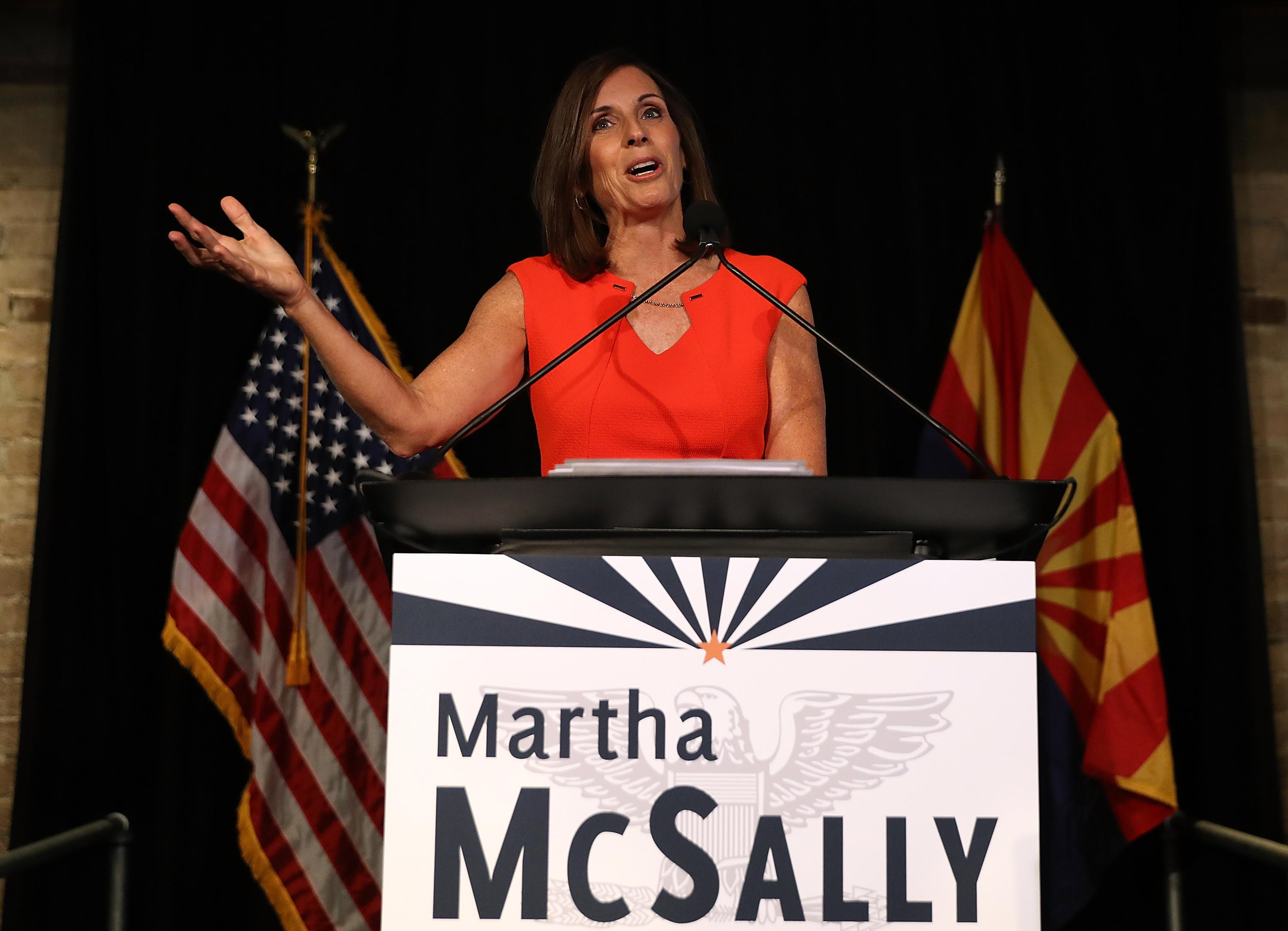 Martha McSally, in a red dress, gestures upward while speaking at a podium.