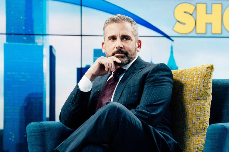 Steve Carell with his hand to his chin and his legs crossed as he sits on the set of The Morning Show.