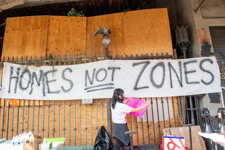 """A person stands underneath a spray-painted board reading, """"Homes not zones."""""""