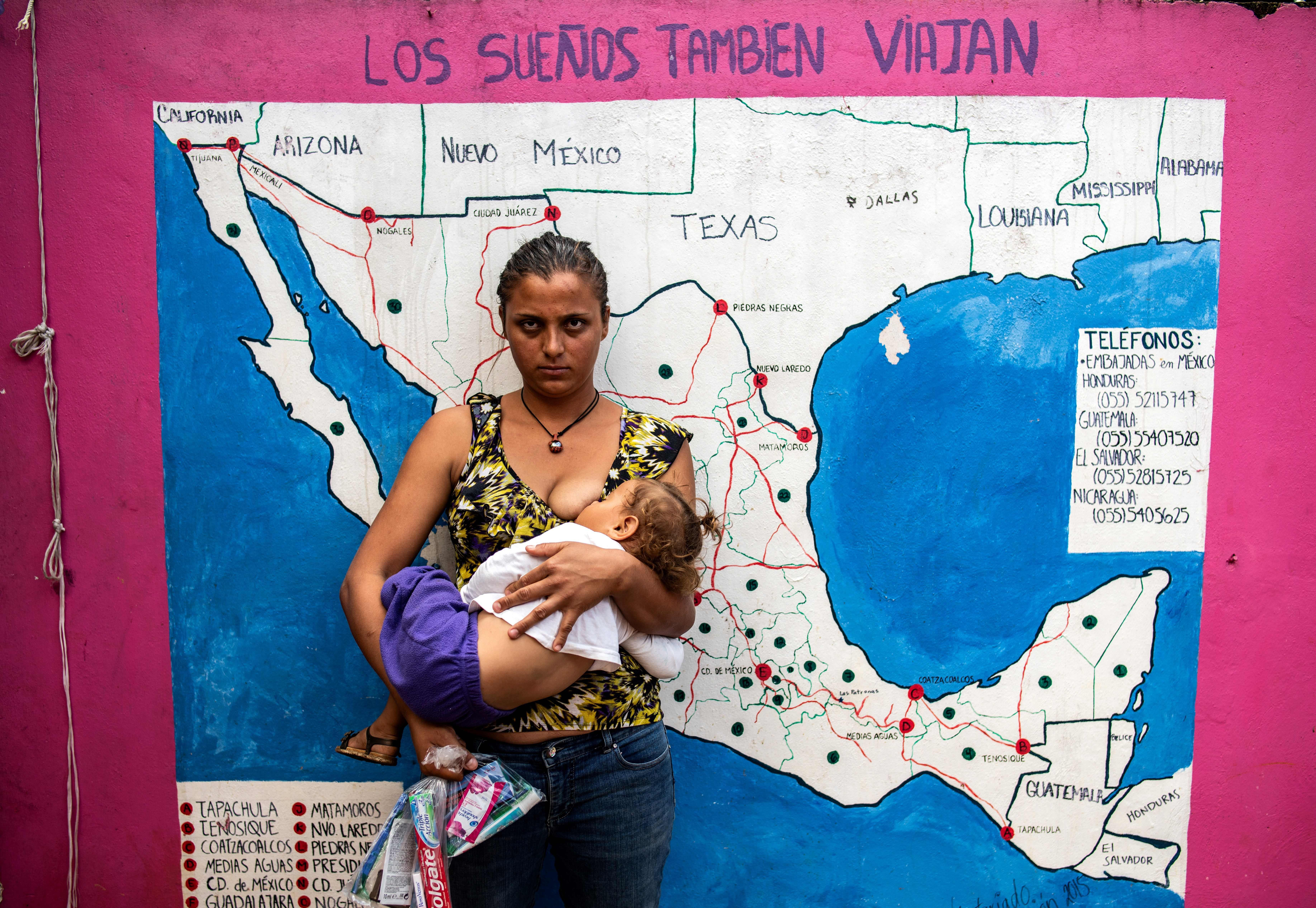 A migrant woman nurses her baby in front of a map of Mexico and the U.S. at a shelter for migrants without documents in Las Patronas town, Veracruz State, Mexico on August 10, 2018.