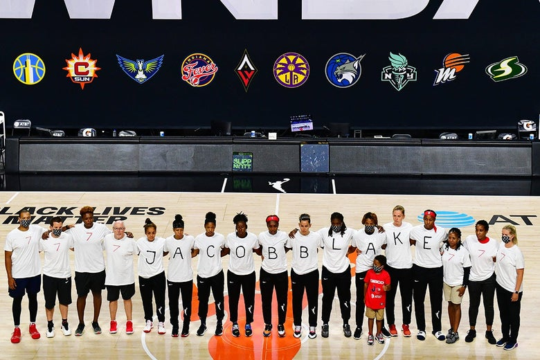 """Mystics players stand in a row wearing shirts that spell out Jacob Blake's name, flanked by people in shirts that read """"7."""""""