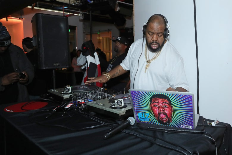 Biz Markie, wearing a white T-shirt and headphones, DJs on a laptop with a blue and pink cartoon image of his own face on it.