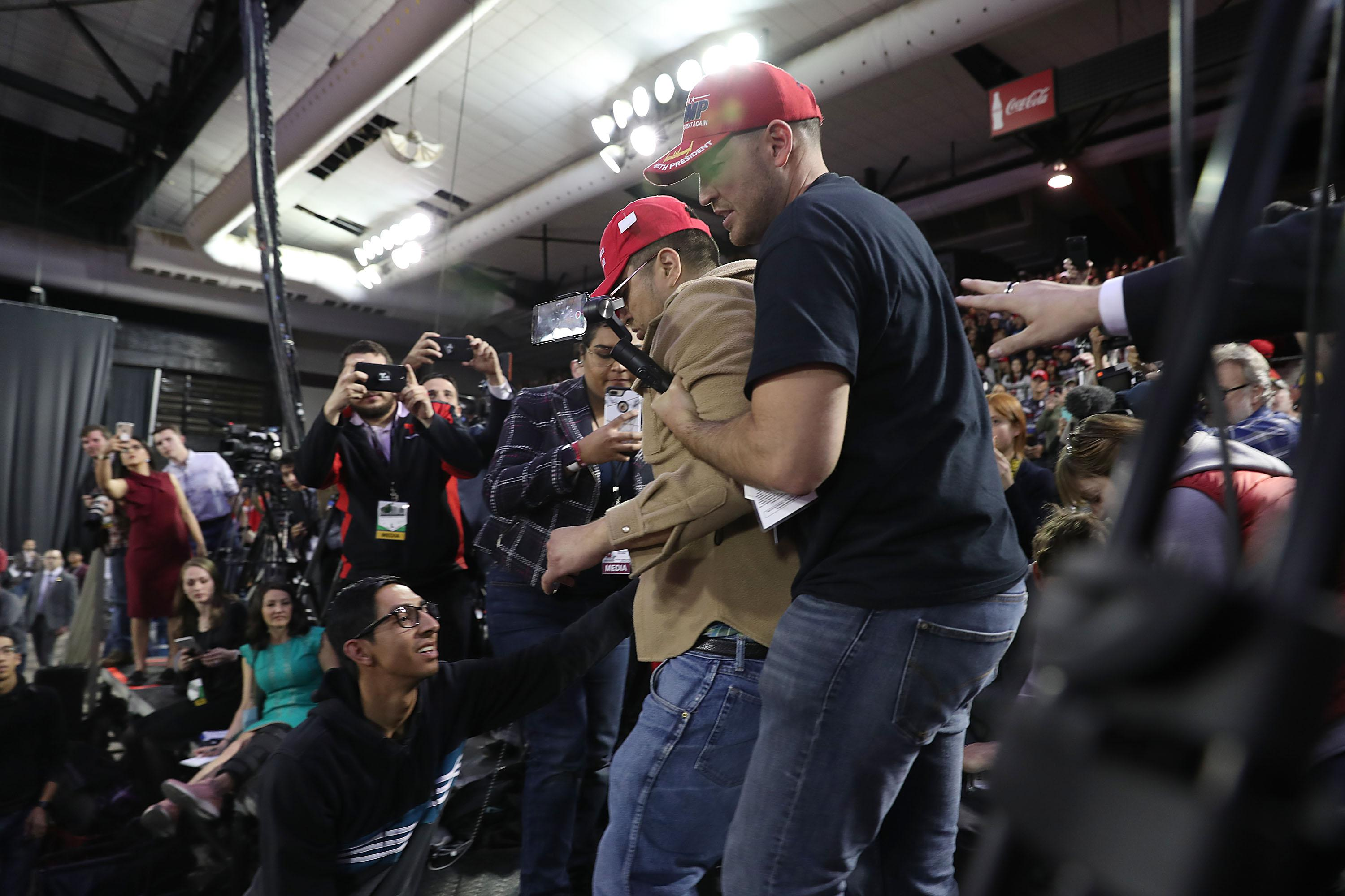 The man, wearing a brown shirt and red MAGA hat, is escorted off the platform, surrounded by reporters with cameras.