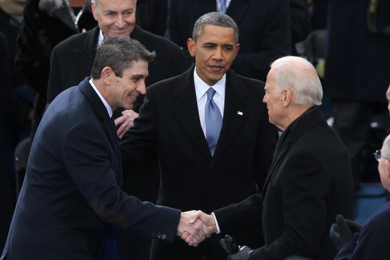 Richard Blanco shakes hands with Joe Biden while Obama stands behind them.