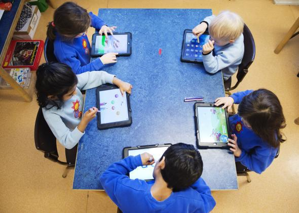 Nursery school students use iPads.