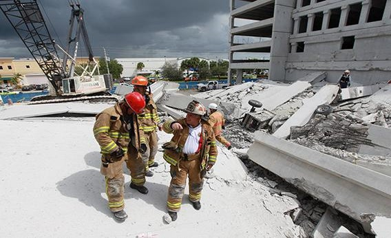 In this handout from Miami-Dade Fire Rescue, Miami-Dade search and rescue look for possible survivors in the rubble of a four-story parking garage that was under construction and collapsed at the Miami Dade College's West Campus on October 10, 2012 in Doral, Florida.