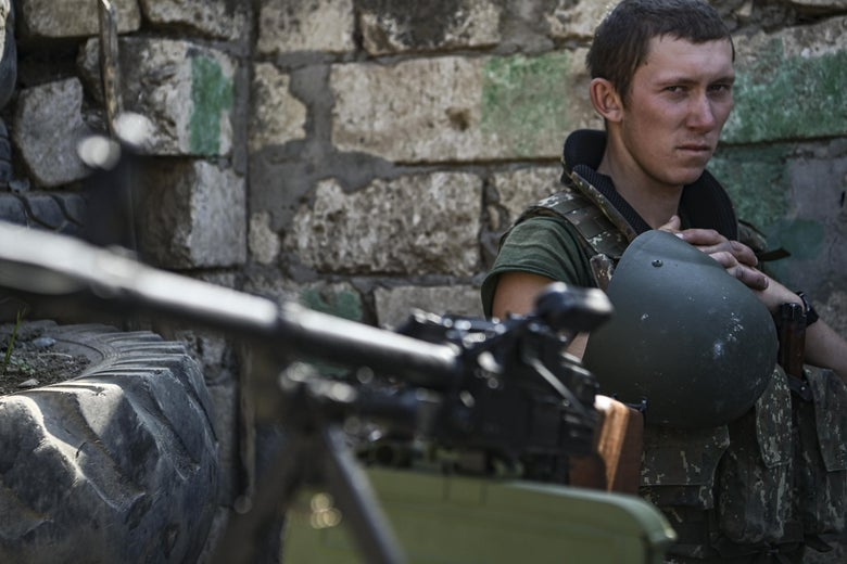 A young soldier with his helmet off looks over his rifle at the camera.