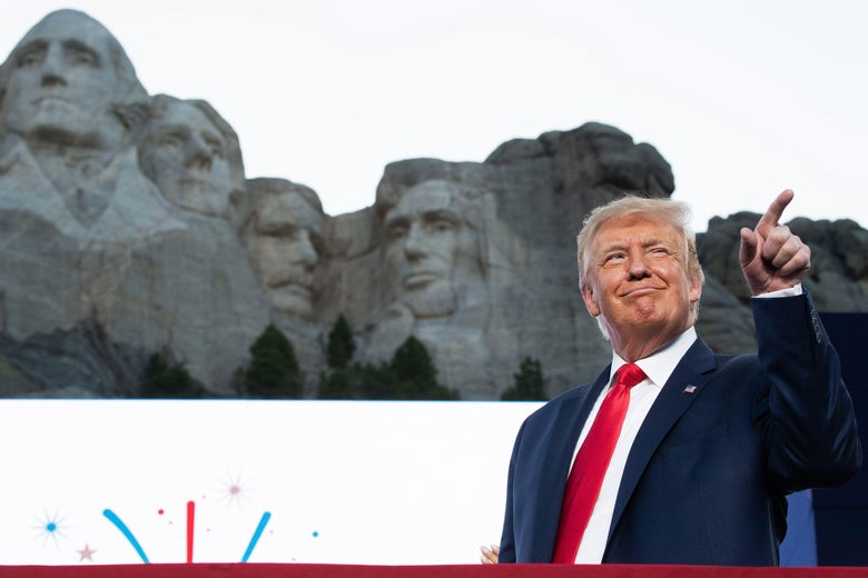 Donald Trump points and smiles while standing in front of Mount Rushmore.
