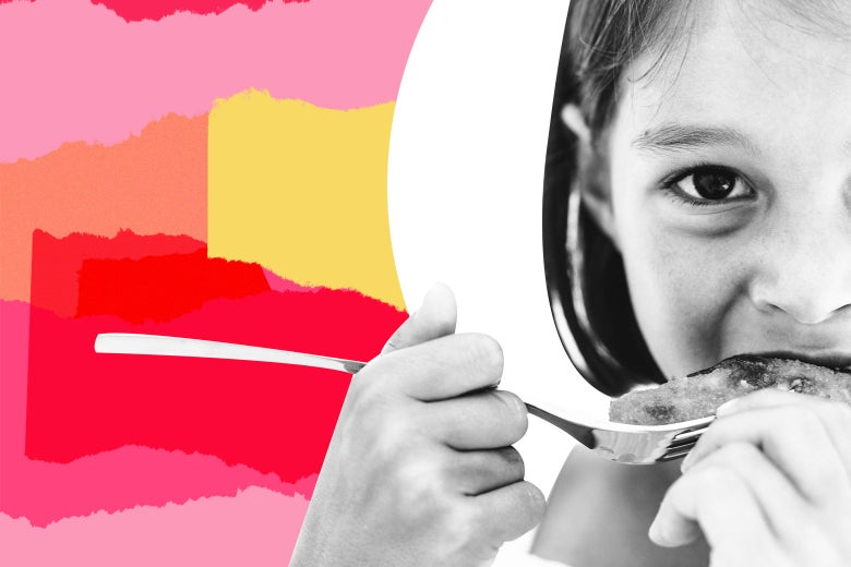 Little girl eating a fish stick off a fork.