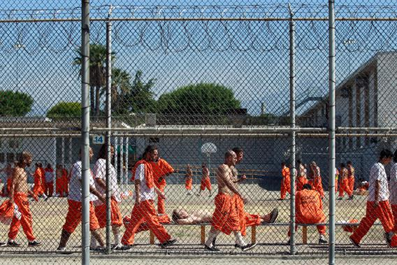 "Inmates walk around an exercise yard at the California Institution for Men state prison in Chino, California, June 3, 2011. The Supreme Court has ordered California to release more than 30,000 inmates over the next two years or take other steps to ease overcrowding in its prisons to prevent ""needless suffering and death."""