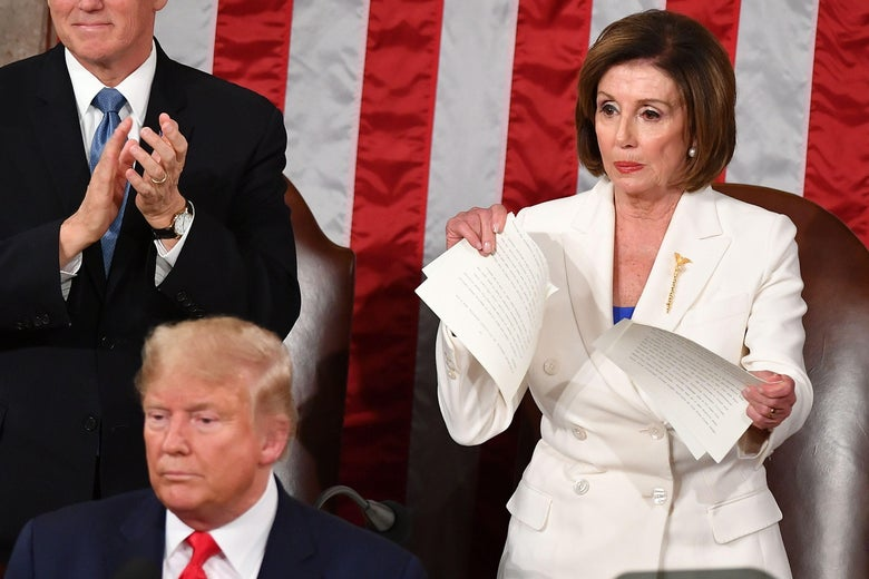 Nancy Pelosi, standing behind Donald Trump, rips apart some sheets of paper.