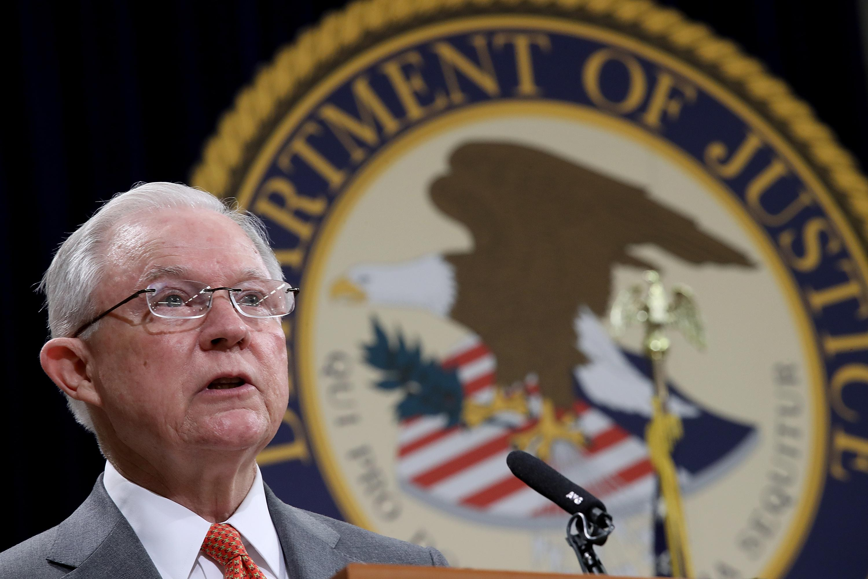 Attorney General Jeff Sessions speaks at podium in front of the Department of Justice seal.