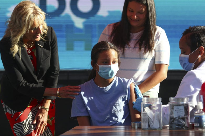 Jill Biden reaches an arm out to a 12-year-old girl wearing a mask who is receiving her COVID-19 vaccination.