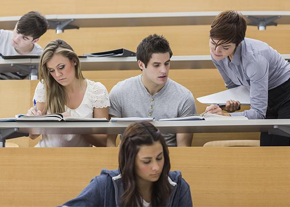 Teacher helping students in lecture hall