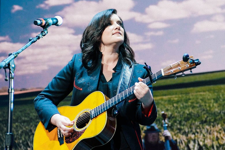 Brandy Clark, holding a guitar, looks to the side as she stands in front of a microphone.
