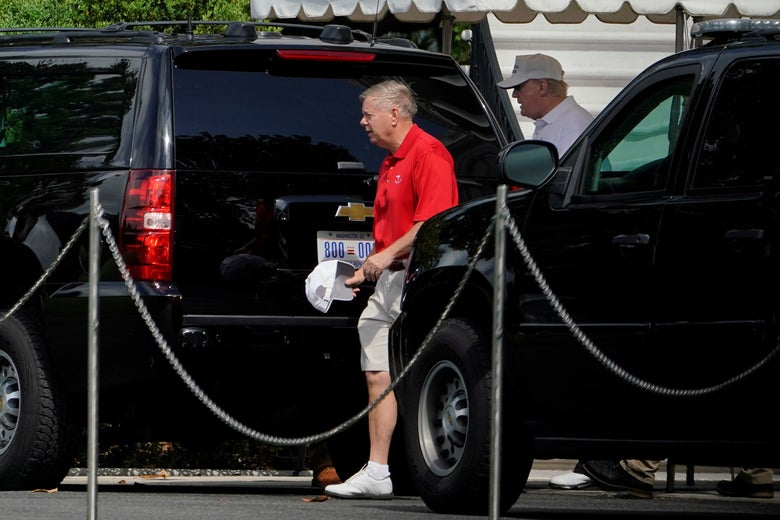 Graham and Trump prepare to board an SUV.