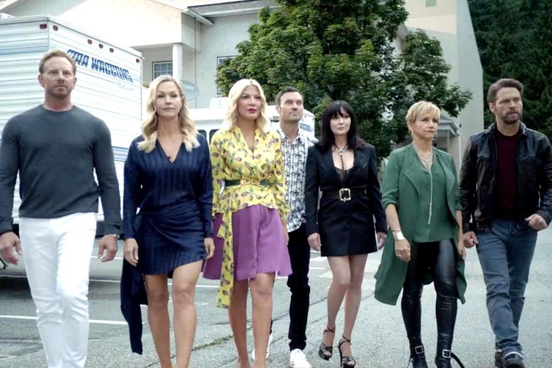 The cast of BH90210 walks toward the camera in a parking lot.