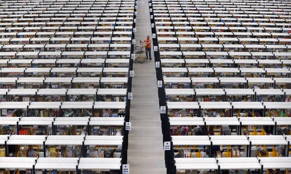 A worker collects orders at Amazon's fulfillment center in Rugeley, central England, Dec. 11, 2012.