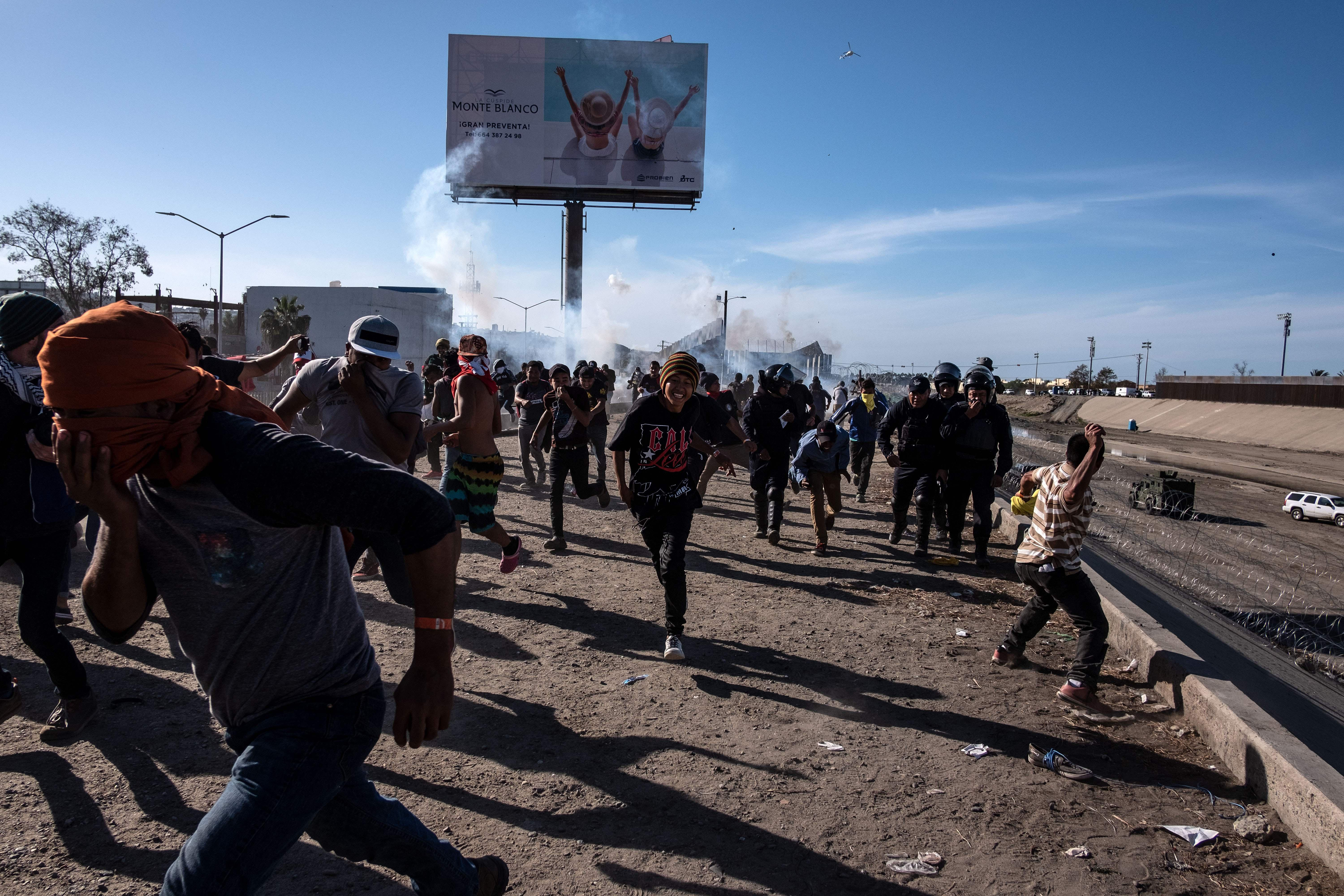 A crowd of migrants, many of them covering their mouths, flee from a cloud of gas behind them.