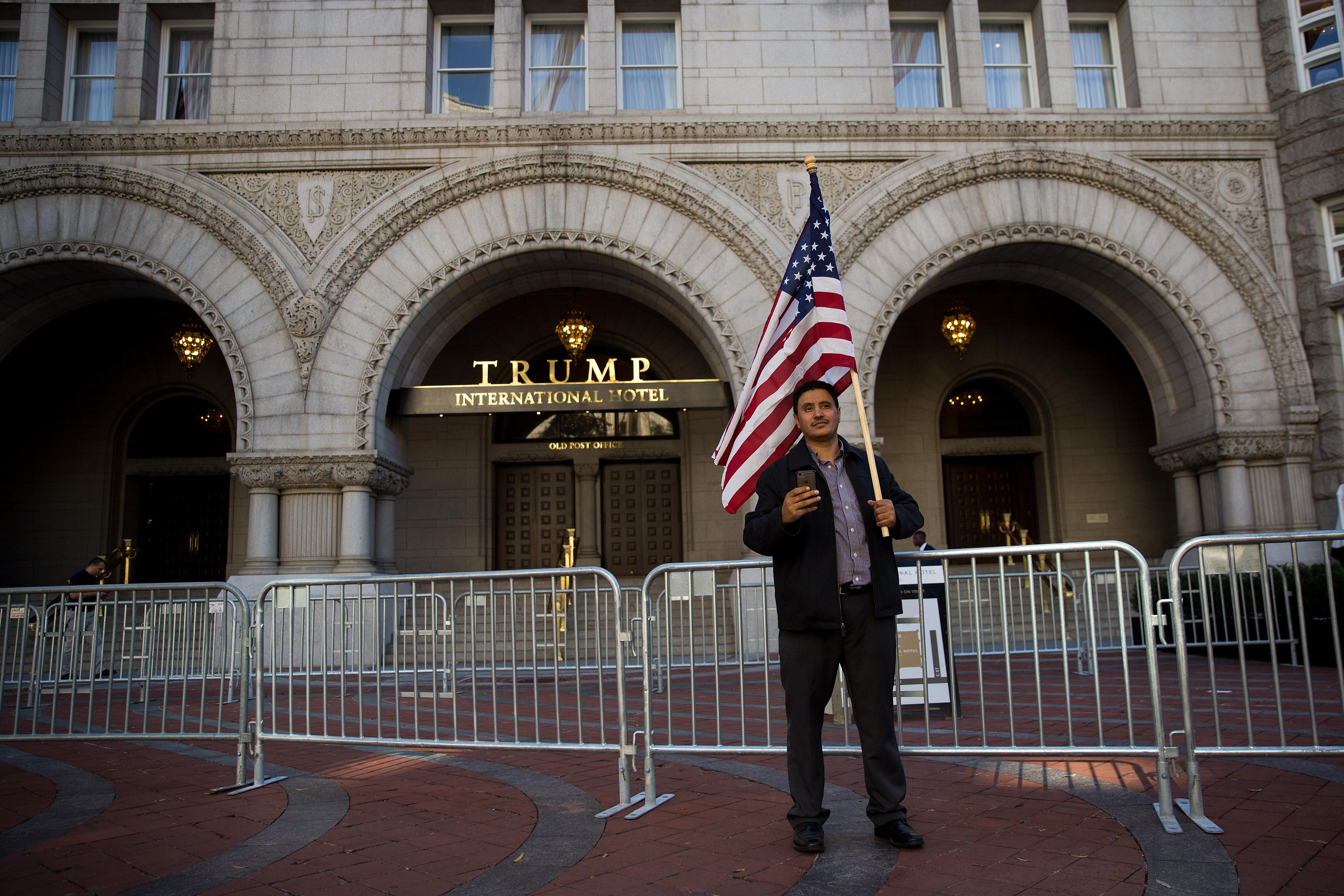 WASHINGTON, DC - OCTOBER 18: A man holds an American flag outside Trump International Hotel following a protest against the Trump administration's proposed travel ban, October 18, 2017 in Washington, DC. Early Wednesday morning, a federal judge in Maryland granted a motion for a preliminary injunction on the administration's travel ban. This is the Trump administration's third attempt to restrict entry into the United States for citizens from mostly Muslim-majority countries. The Department of Justice said it plans to appeal and the White House issued a statement calling the judge's decision 'dangerously flawed.' (Photo by Drew Angerer/Getty Images)