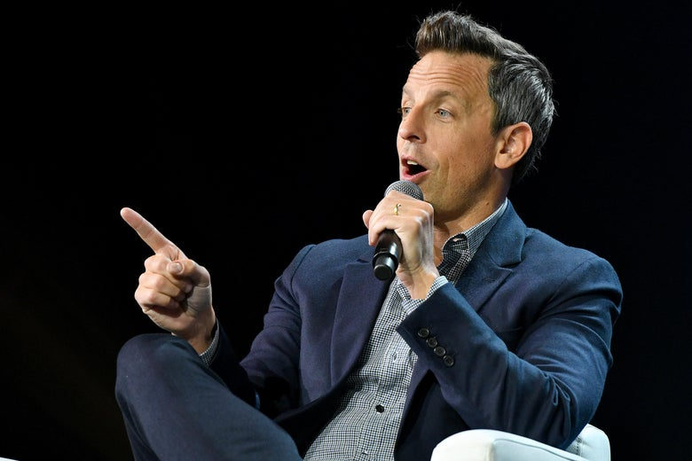 Seth Meyers, Host Late Night with Seth Meyers, holds a microphone and points his finger in front of a black backdrop.