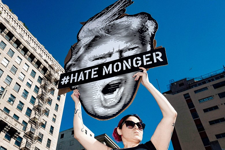 A protester holds up a sign with Donald Trump's face and the words #Hate Monger.