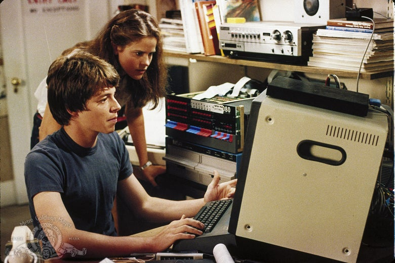 Matthew Broderick looks at an early 1980s computer while Ally Sheedy looks over his shoulder.